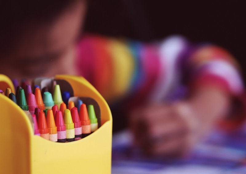 Close up view of a box of crayons with girl in the background coloring