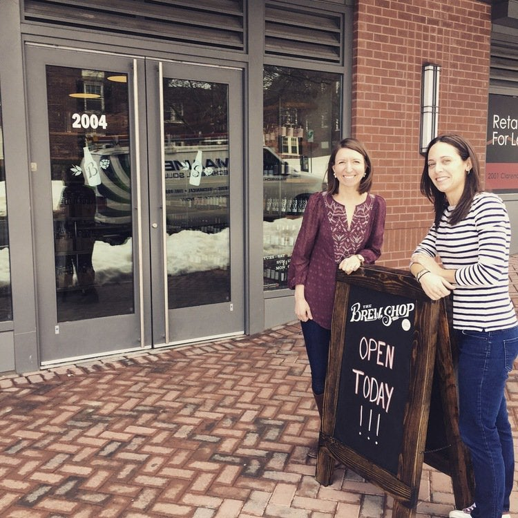 Two founders stand in front of their Virginia-based beer shop