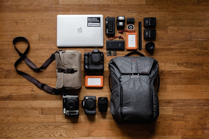 A photographer's equipment, including multiple cameras, a laptop, and two bags, lay on a hardwood floor.