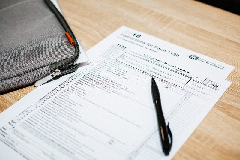 A blank corporate tax return form sits on a wooden desk.