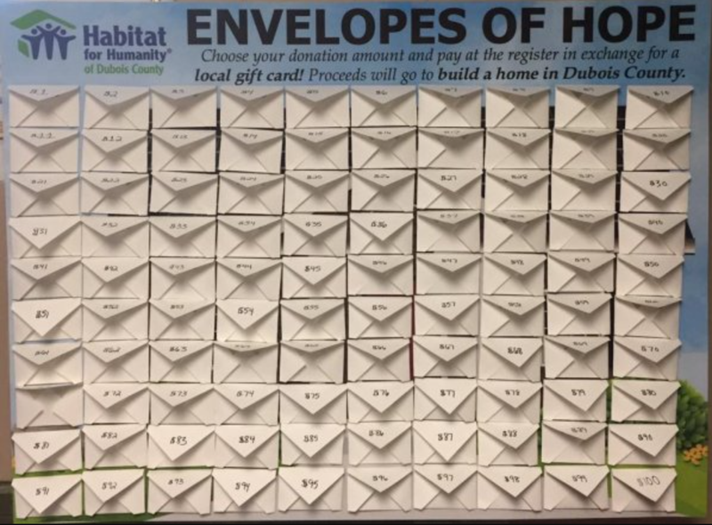 """Photo of 100 envelopes taped to a wall under the Habitat for Humanity of Dubois County logo and a title reading """"Envelopes of Hope"""" with a description of the process."""