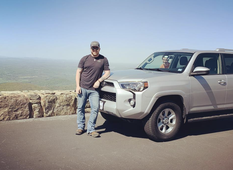Man leaning on a Toyota SUV with a scenic view in the background.