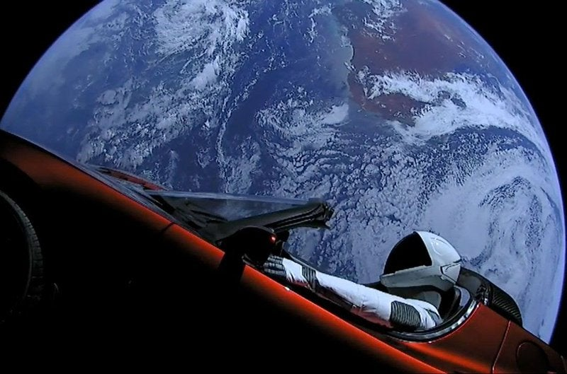 Tesla advertisement with picture of an astronaut in a red Tesla with Earth in the background.