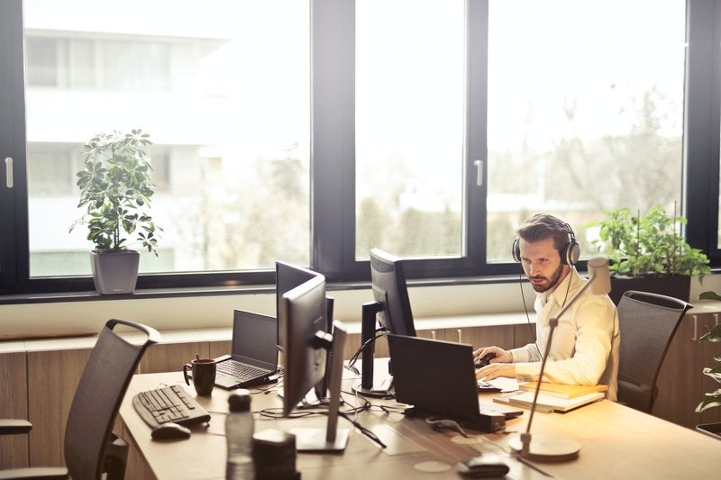 An office worker uses a phone headset and multiple screens.