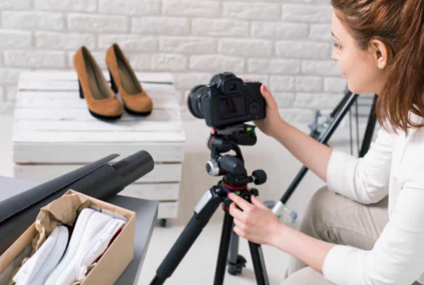 Picture of a woman using a tripod to take a picture of shoes.