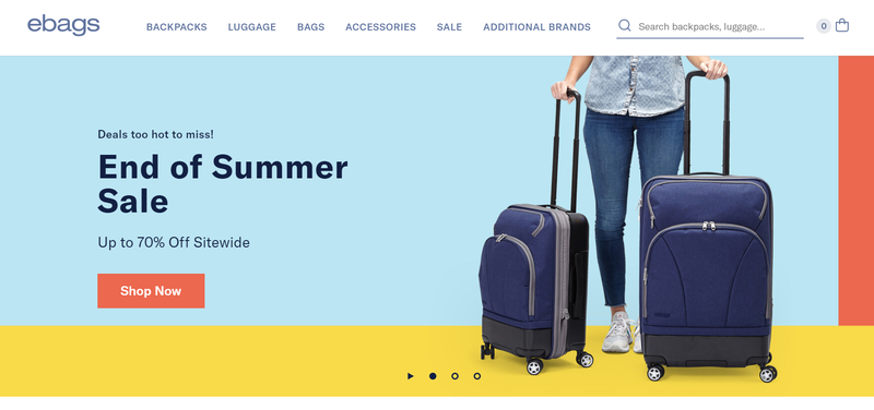 Summer sale promotion on a computer screen featuring a woman holding two suitcases.