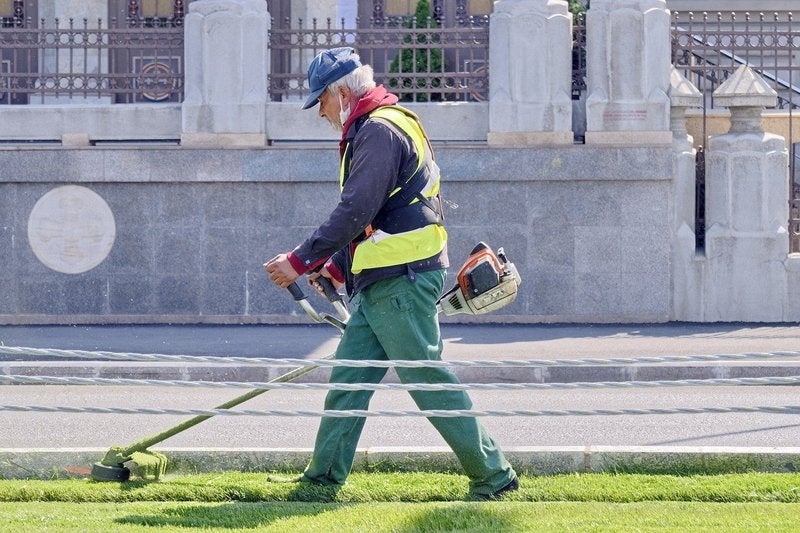 A worker uses a string trimmer on a lawn.