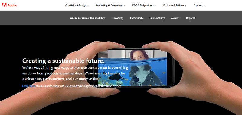 A note about sustainability on the Adobe website set over two hands holding a smartphone.