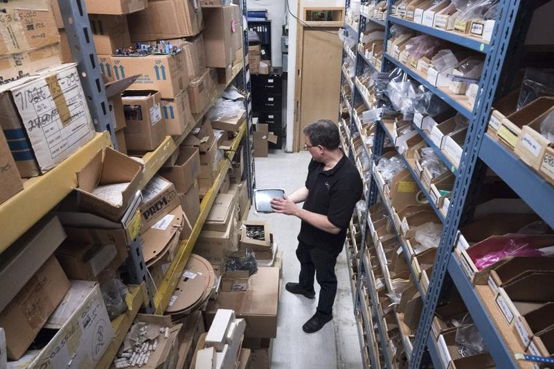 A store owner stands reviewing an overwhelmingly disorganized inventory shelf.