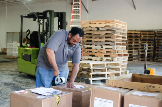 A manufacturer tapes up the last boxes for a shipment of finished goods going to a retailer.