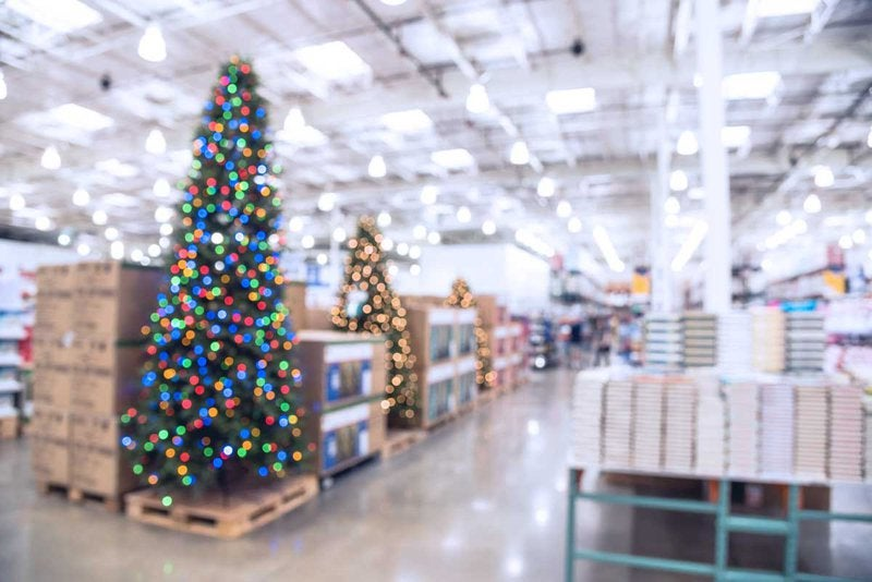 A Christmas tree and other holiday items sit out in a retail store.