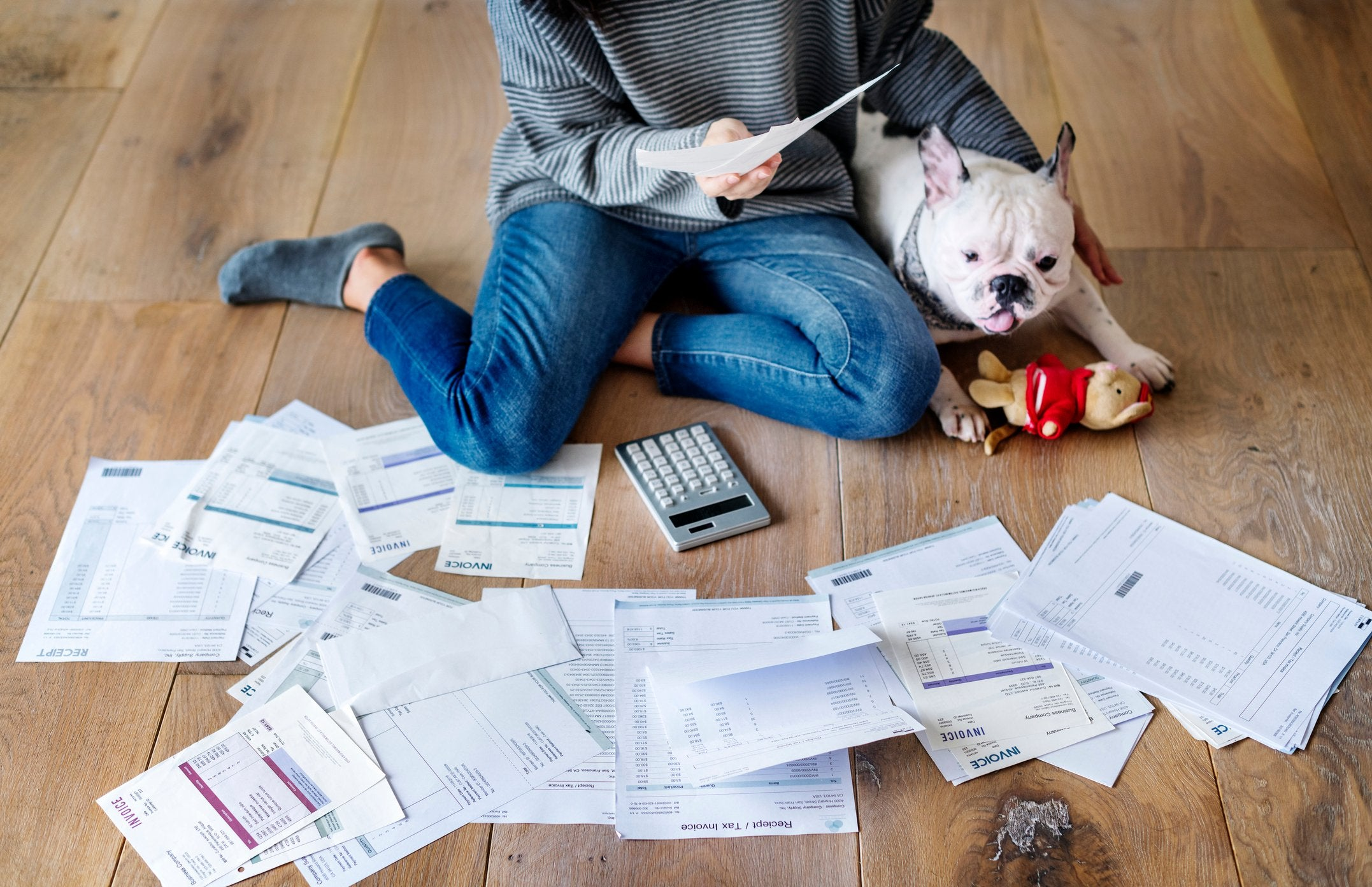 A woman sits on the floor next to her French bulldog and looks at a pile of bills.