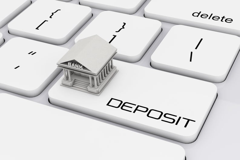 Keyboard with Deposit button and a bank on top of it.