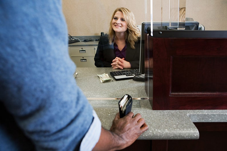 A bank teller smiles to a customer from behind her desk.