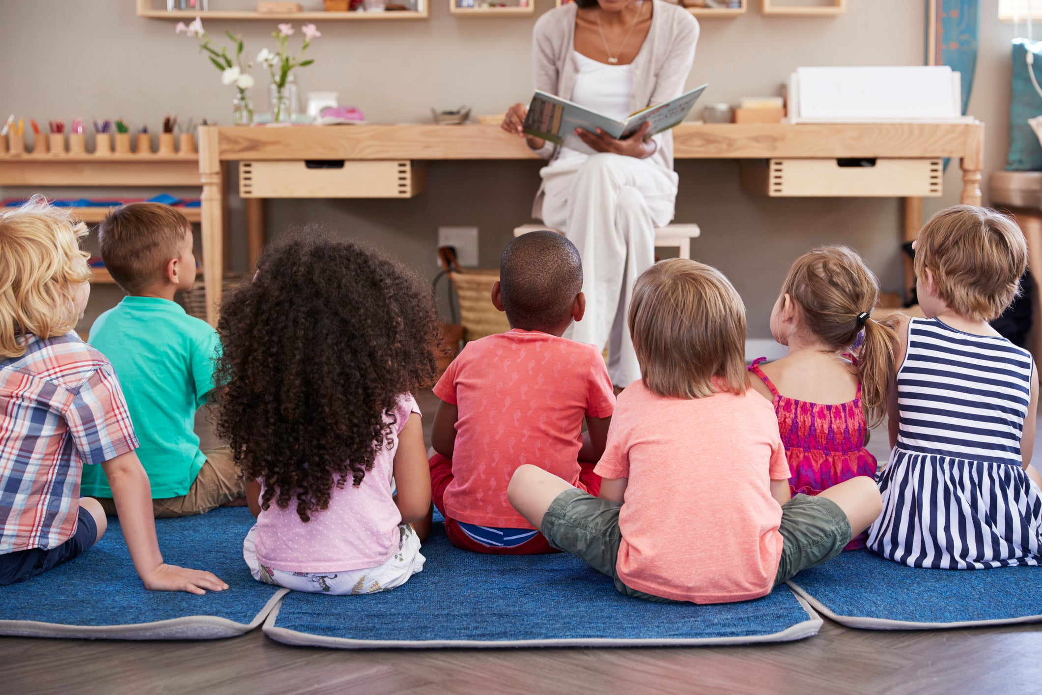 A group of children sitting on mats in a child care center listening to a story.