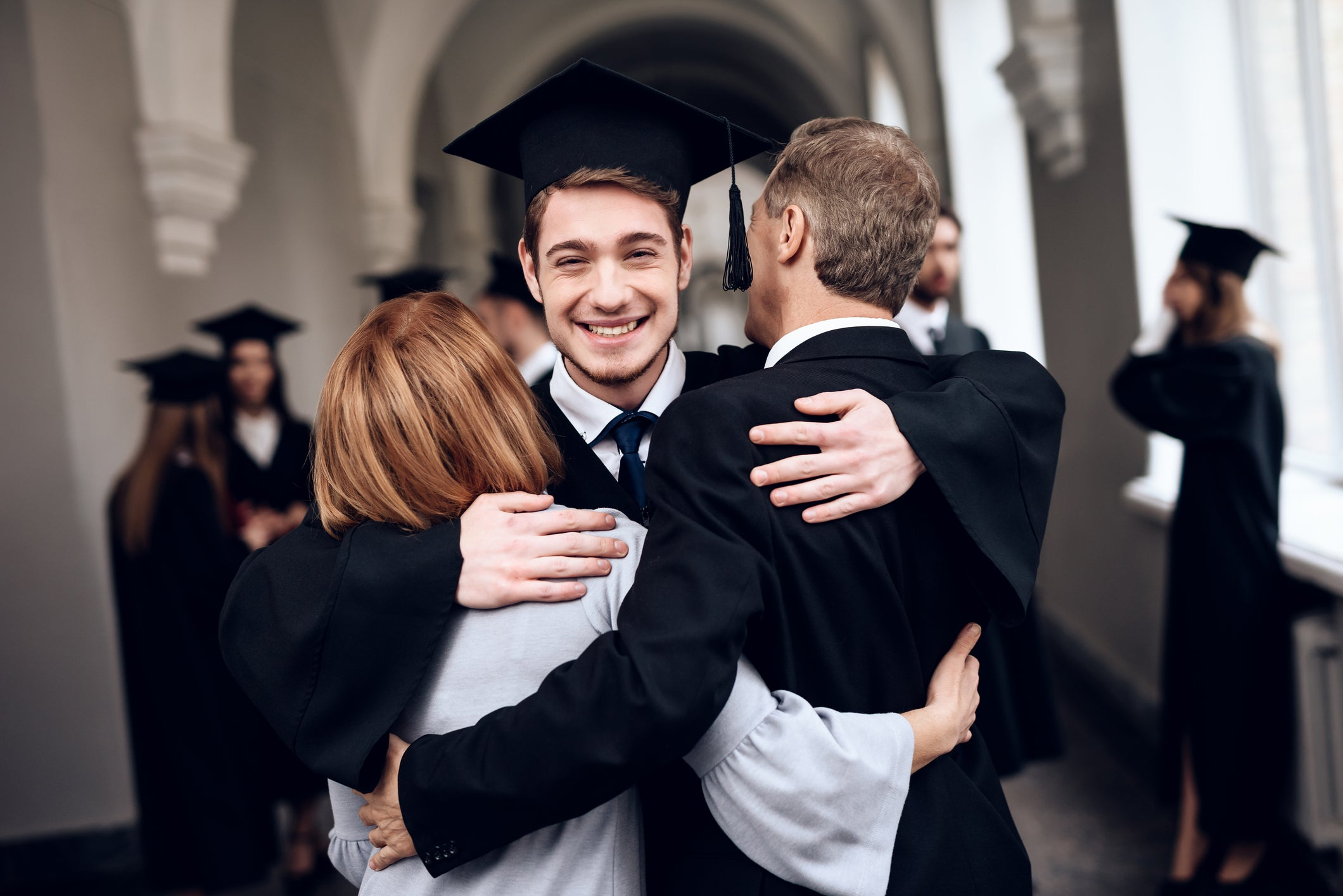 Male college grad hugging his parents.