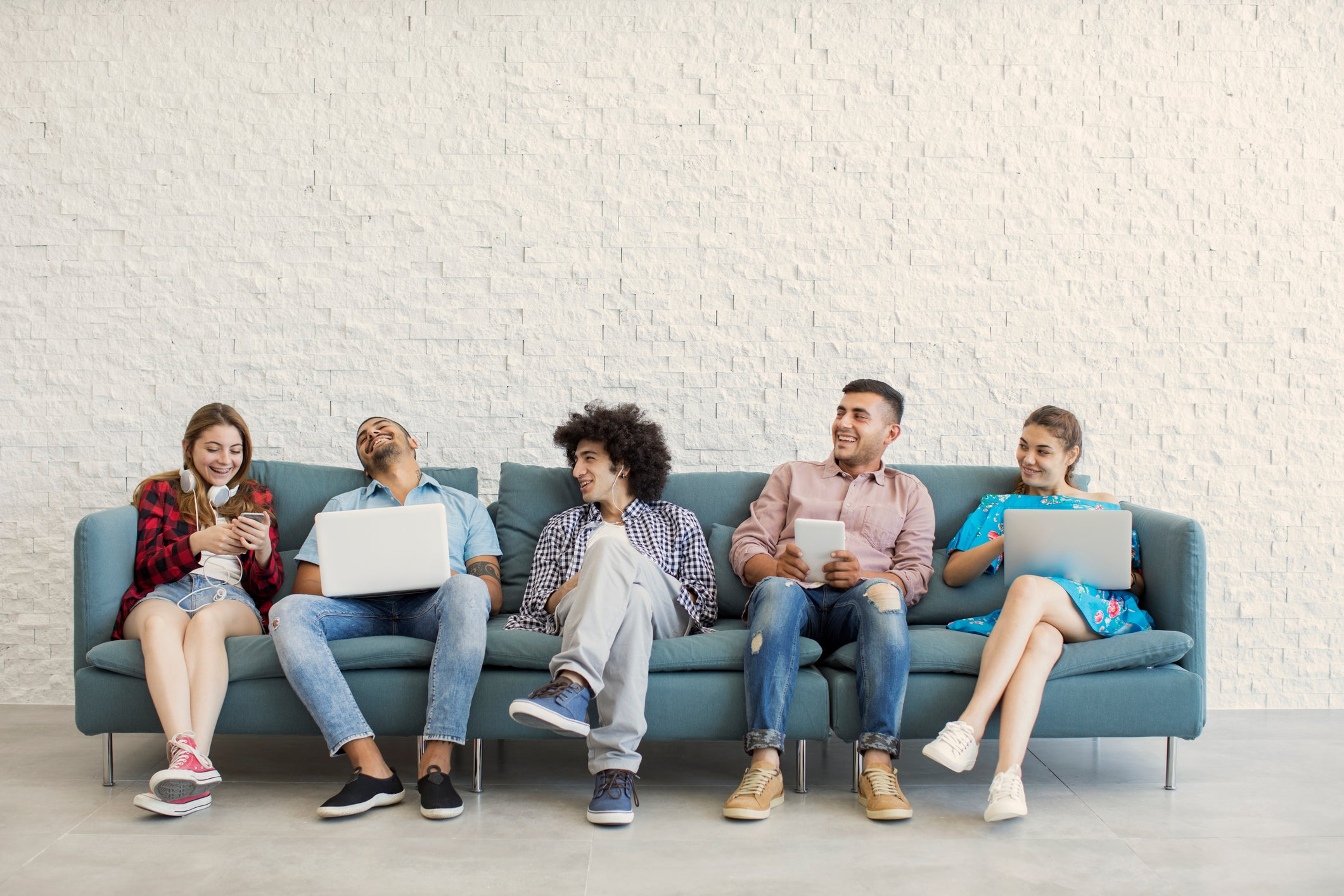 A group of college-age friends on a couch with laptops or phones.