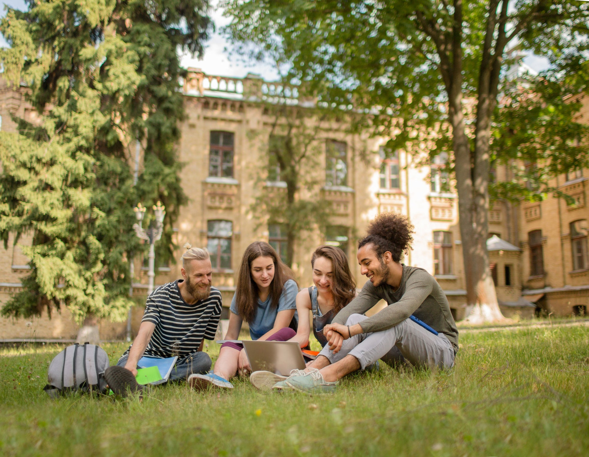 College students studying on the grass in front of a large school building.