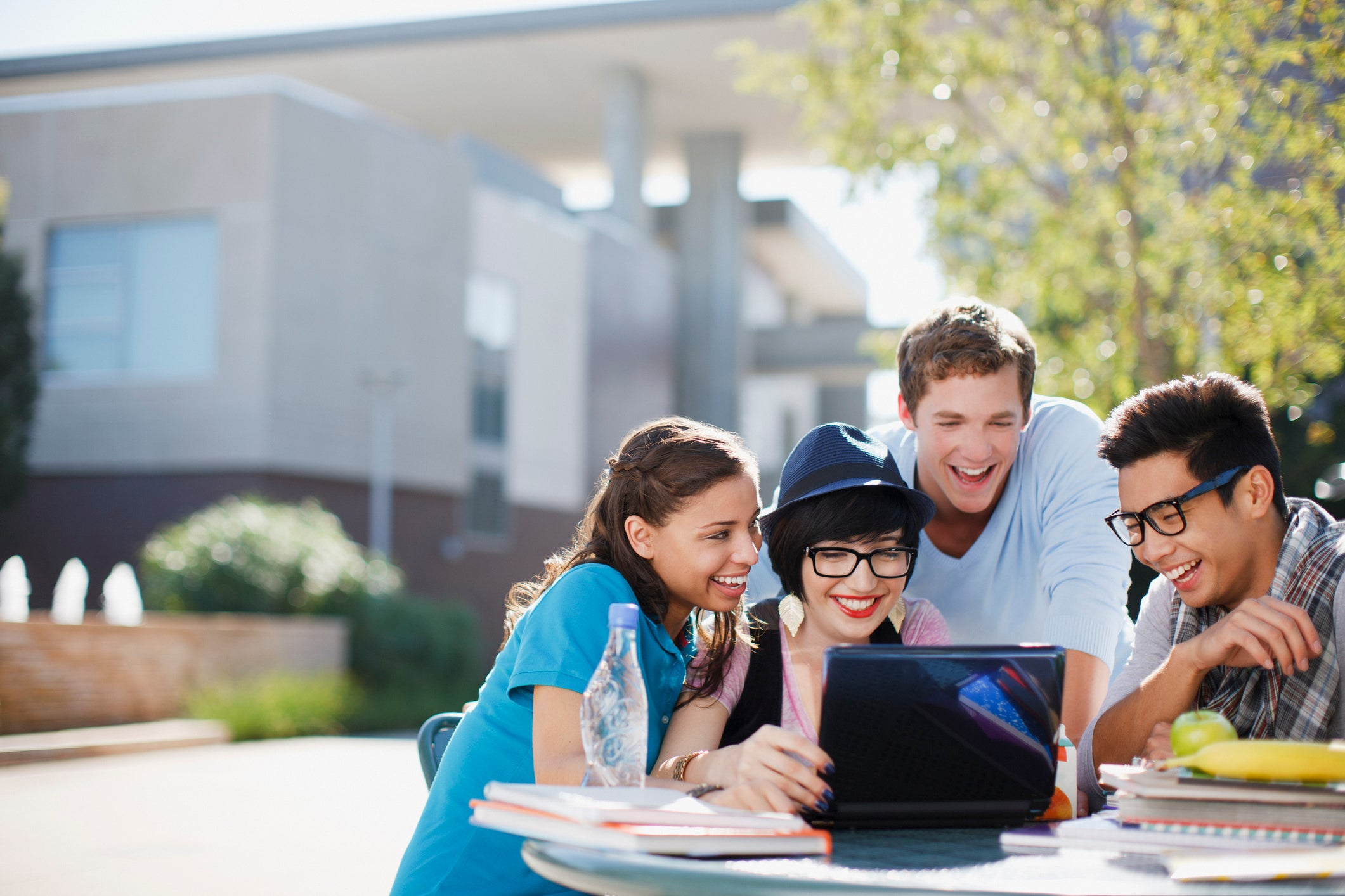 Smiling college students gathered around laptop at an outdoor table.