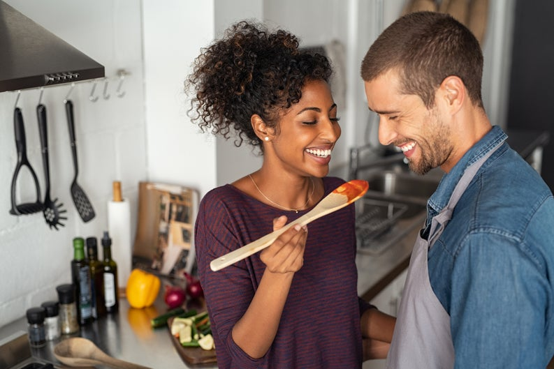 A young couple laughing and cooking at home.