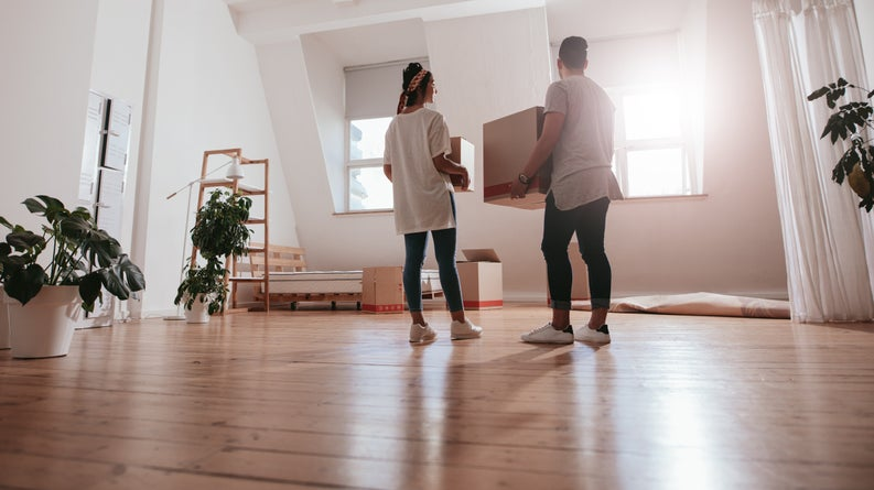 A young couple moving boxes and plants into a new apartment.