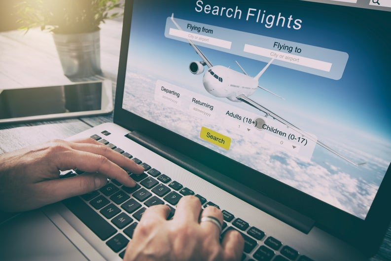 Man using laptop to search for flights.