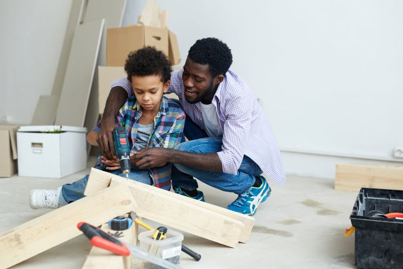 A father and child working on home improvements together.