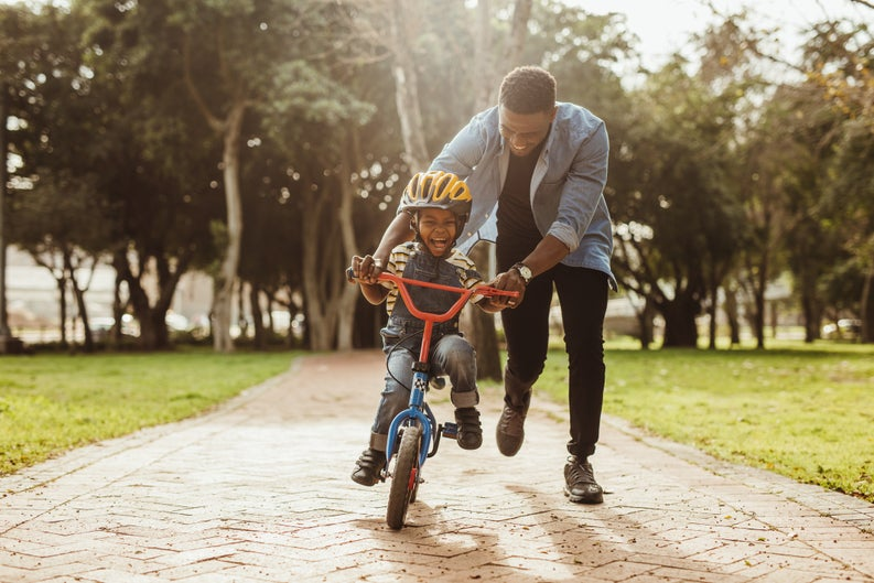 A dad helping his laughing young son ride a bike through a park.