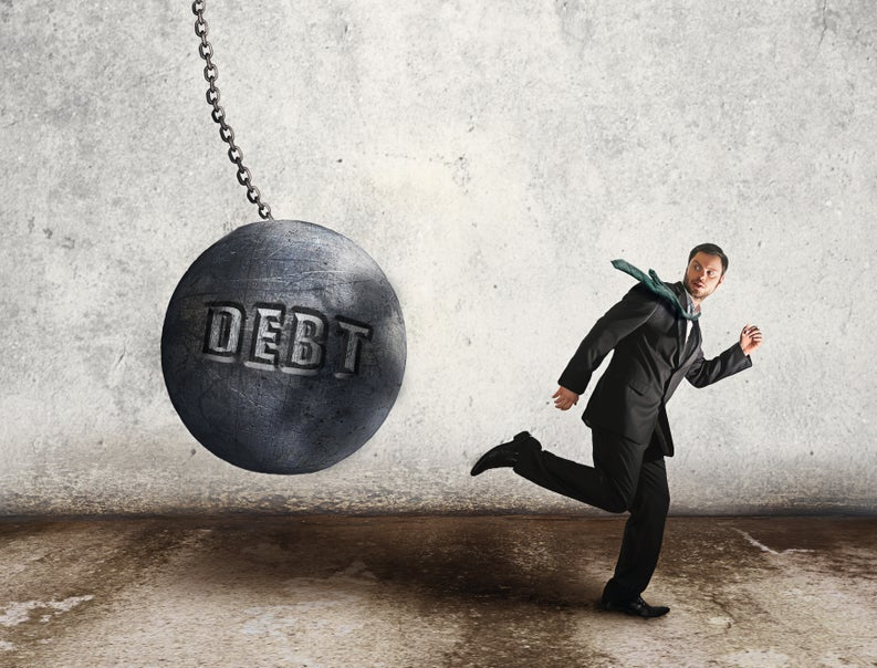Man in suit running from a wrecking ball labeled Debt.