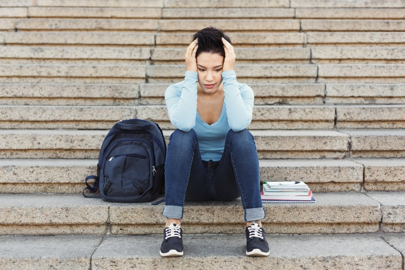 Young woman sitting on steps next to a backpack and books with her head in her hands