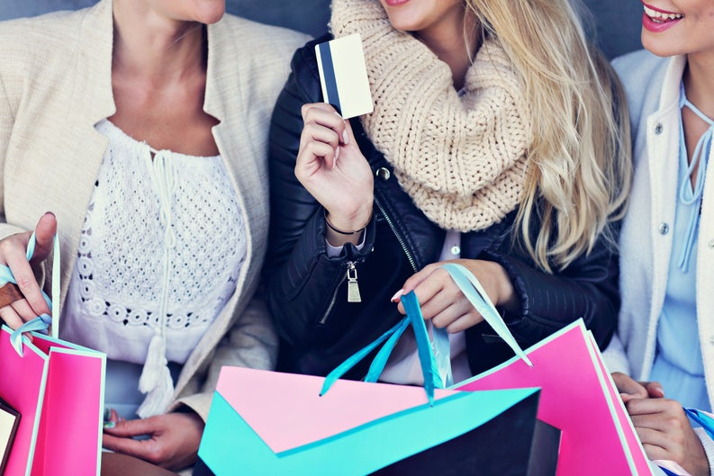 Three women holding shopping bags, one holding a credit card