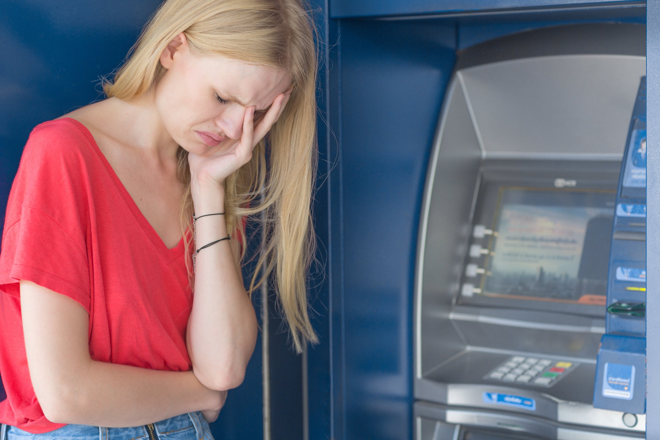 Young woman in despair beside ATM.