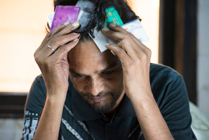 Man having a mental breakdown while clutching two big fistfuls of credit cards to his head.