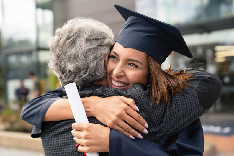 Young woman in graduation cap beaming as she hugs her mother.