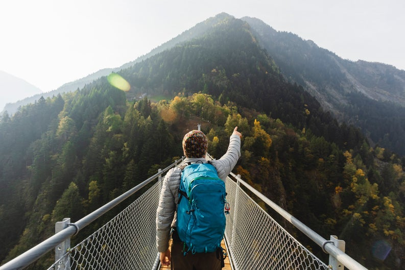 Man in puffer jacket and parka crossing narrow bridge over forest and pointing intrepidly at mountain in distance.