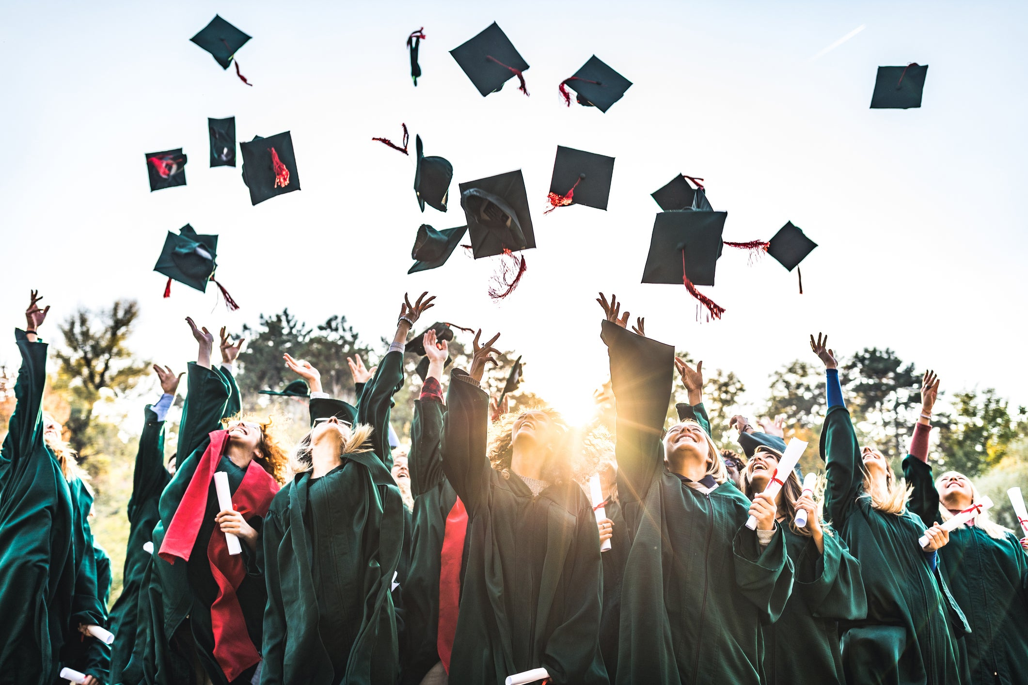A bunch of graduates throwing their caps into the air.