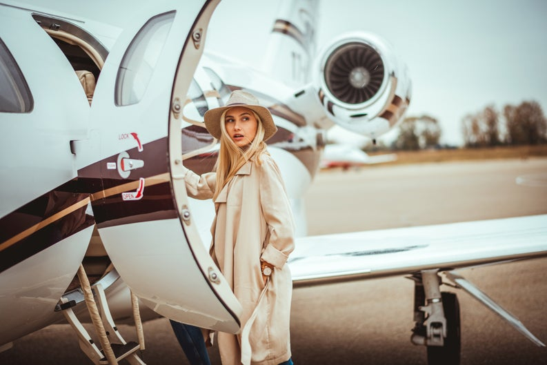 Young woman about to step into private plane.