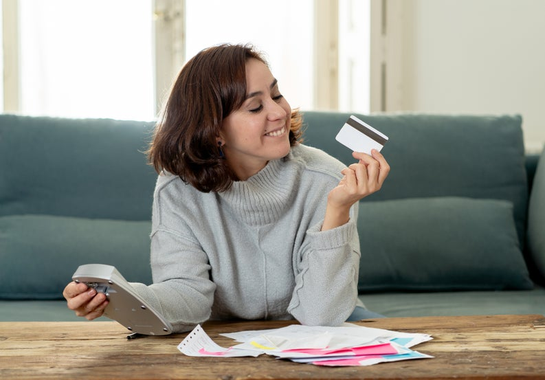 Young woman holding a calculator and a credit card and grinning with satisfaction at the credit card.
