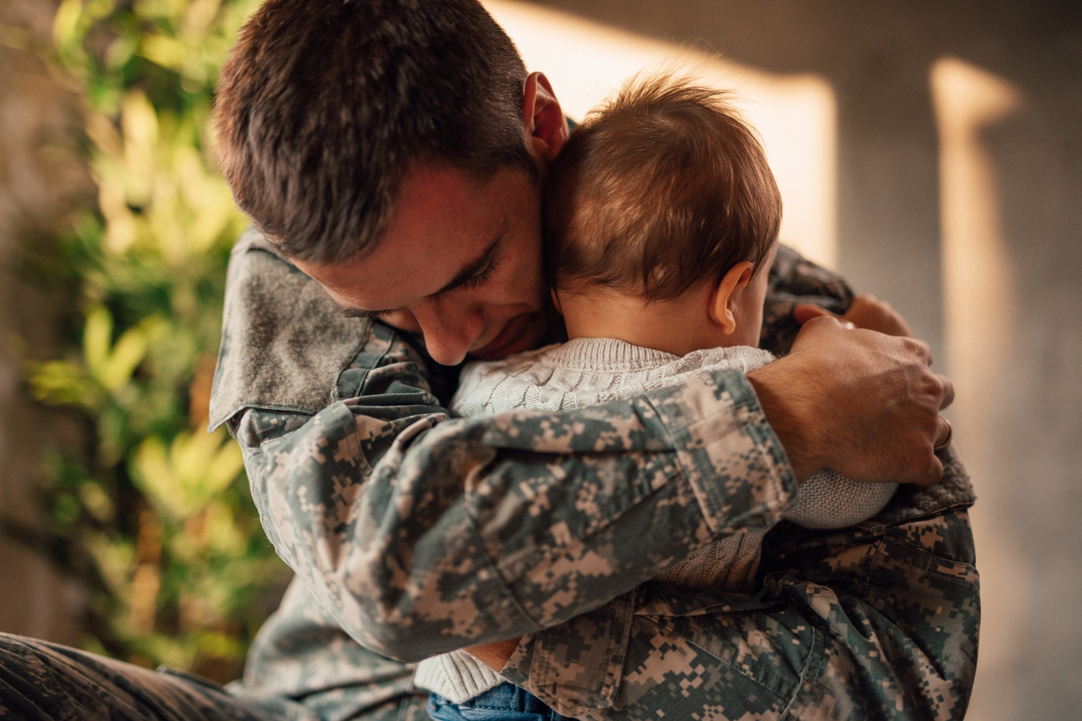 Military father embracing infant son.