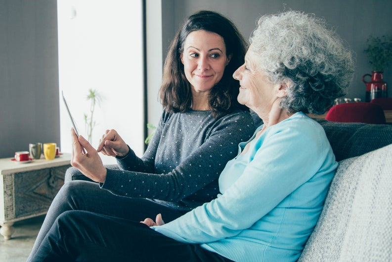 Middle-aged woman showing document to an older woman, possibly her mother.