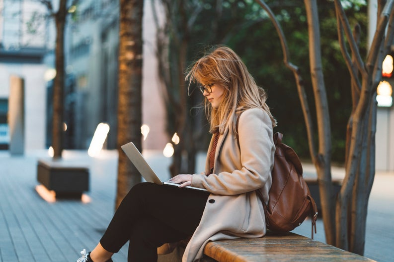 Young bespectacled woman sitting on college campus bench and working on laptop.