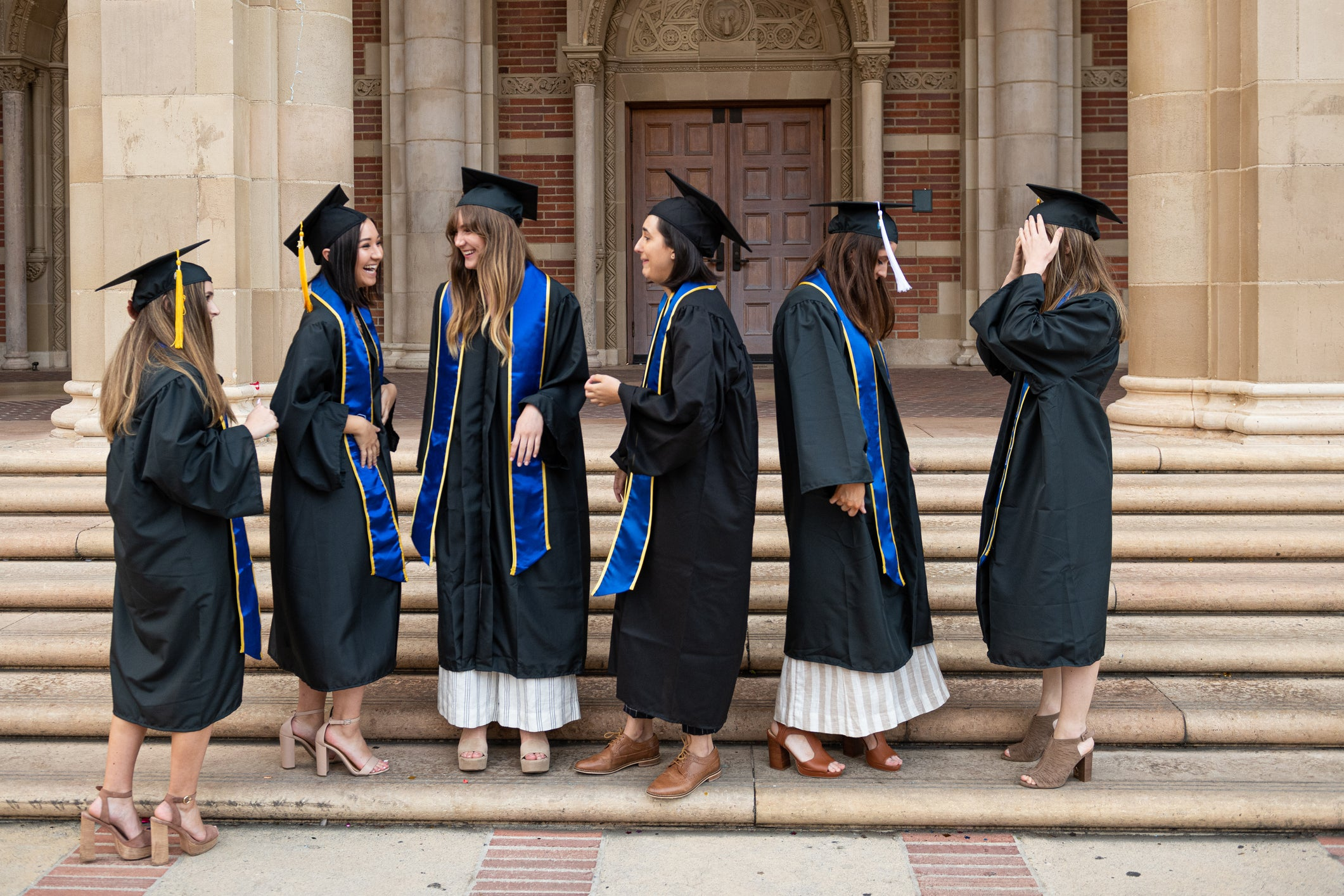 A group of six young women in graduation caps and gowns talking animatedly.