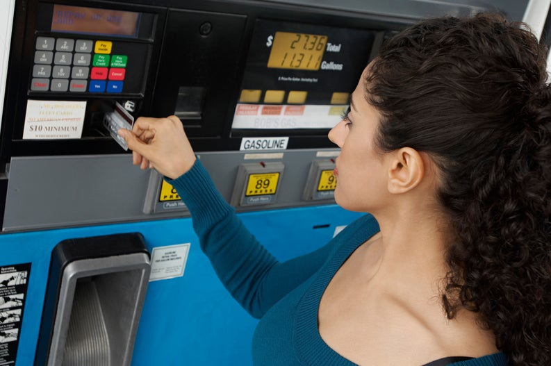 woman putting a credit card into a gas pump