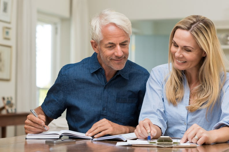 Middle-aged man and woman looking at paperwork on table and smiling