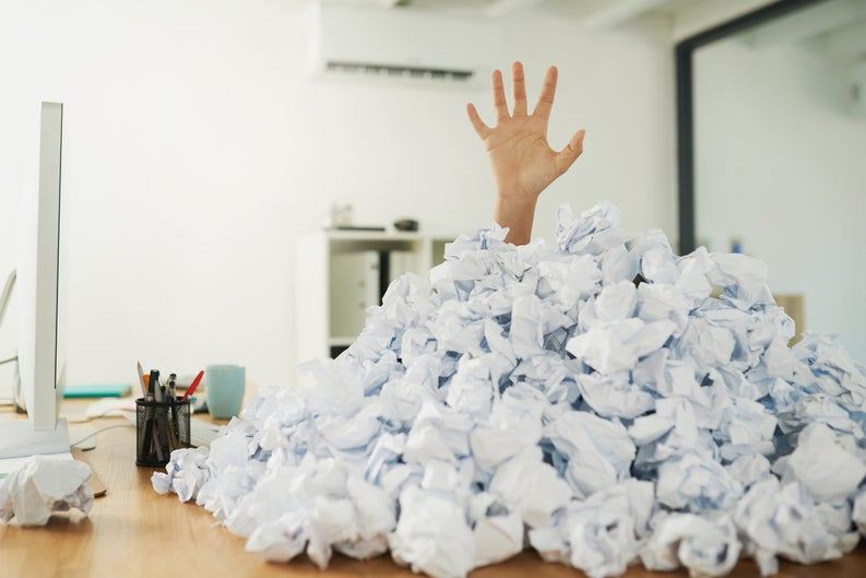 A hand reaching out from beneath a pile of crumpled-up balls of paper.