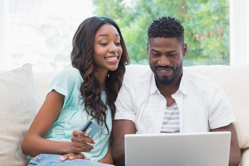 young man using laptop and young woman holding credit card sitting next to each other on a couch.