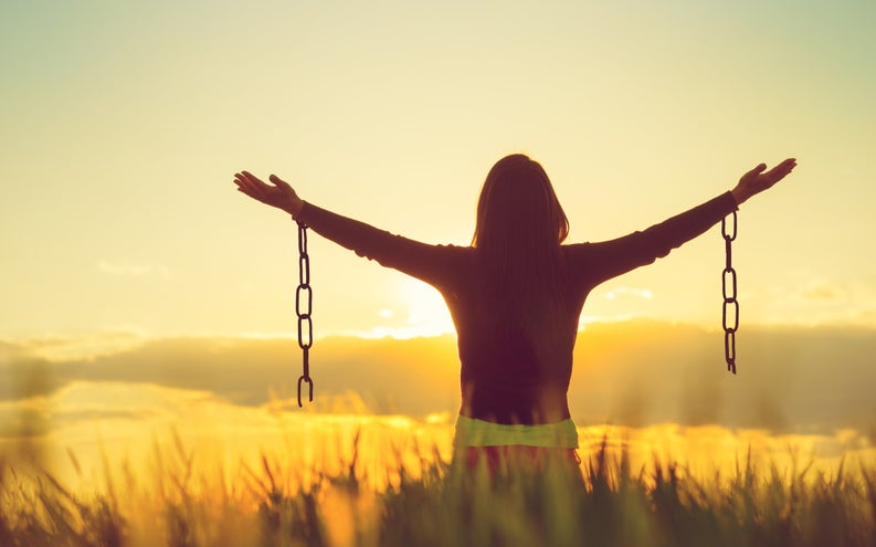 Woman standing in open field at sunset with broken chains hanging from outstretched arms.