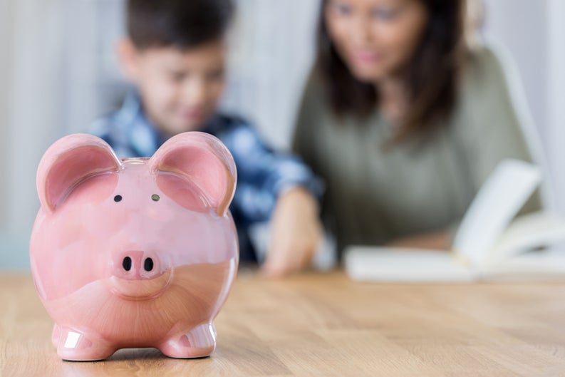 A piggy bank with a mother reading to her son in the background.