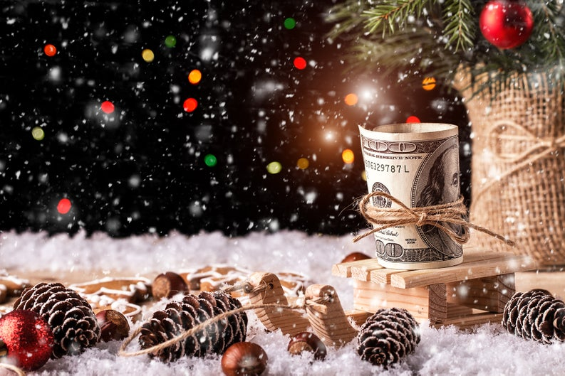 A 100-dollar bill tied with a thin rope amid snow, pine cones, and Christmas ornaments.