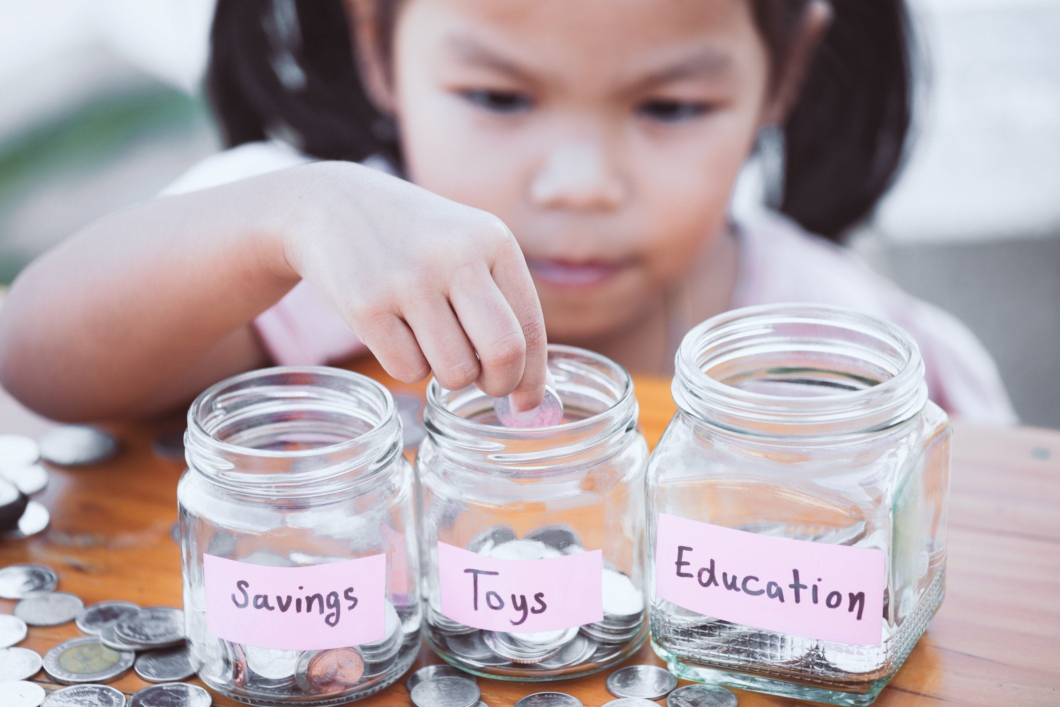 A small child depositing change into three jars labeled savings, toys, and education.